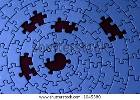 jigsaw in blue with five missing pieces - focus is on the center
