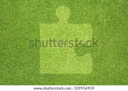 Jigsaw on green grass texture and  background