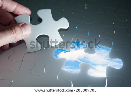 Jigsaw piece with sky in hole, conceptual image