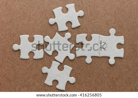 jigsaw puzzle on brown wooden - stock photo