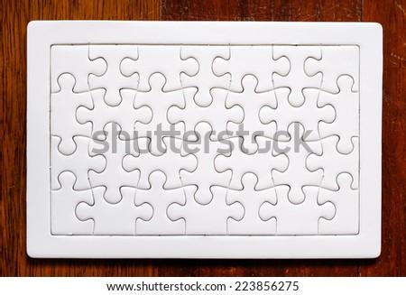 Jigsaw puzzle on wood background - stock photo