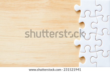 Jigsaw puzzle on wood for business concepts - stock photo