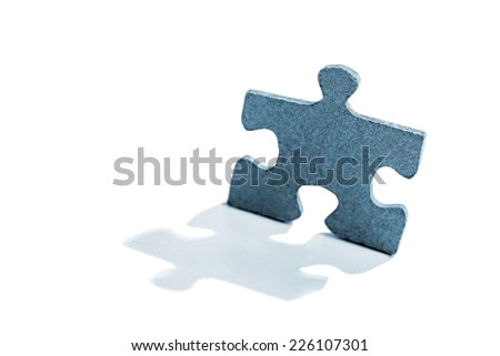 Jigsaw puzzle piece in shape of a standing man lit by the backlight on a white background. Shallow depth of field - stock photo