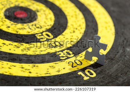 Jigsaw puzzle piece in shape of a walking man moving towards center of old target - stock photo