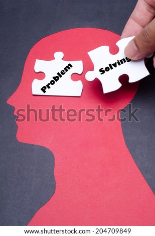 """Jigsaw puzzle pieces and black paper project as a outline of human head with """"Problem Solving"""" word - stock photo"""
