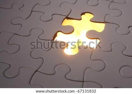 Jigsaw puzzle placed over light. - stock photo