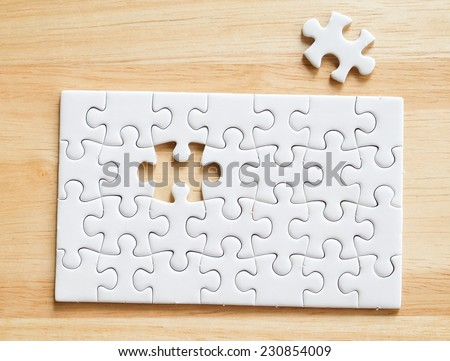 Jigsaw puzzle with missing one piece on wood, for business concepts - stock photo