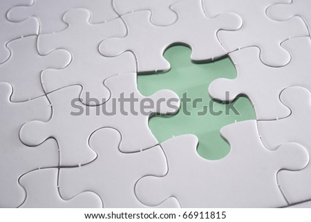 Jigsaw puzzle with missing piece isolated on green background. - stock photo