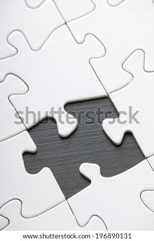 Jigsaw with Blank white pieces and one part missing - stock photo