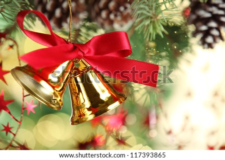 Jingle bell hanging from christmas tree - stock photo