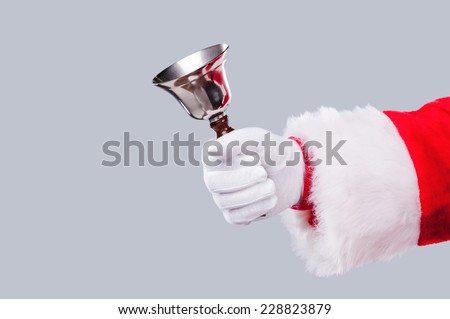 Jingle bells! Close-up of Santa Claus holding metal bell in his hand and against grey background - stock photo