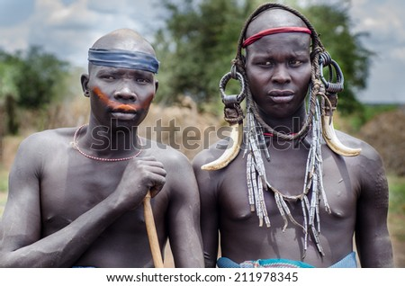 JINKA, ETHIOPIA - AUGUST 10: portrait of unidentified Mursi men on August 10 2014. Mursi people wear many ornament made by natural materials - stock photo
