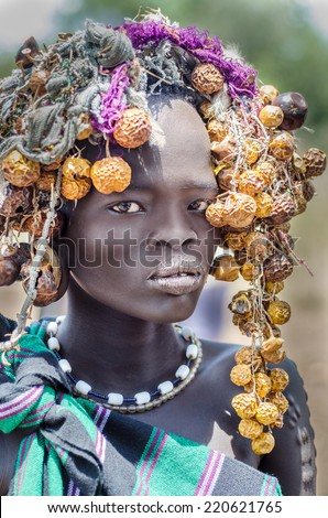 JINKA, ETHIOPIA - 10 August: unidentified girl from Mursi tribe in Mago National Park, Jinka, on 10 august 2014. Mursi people paint their bodies and use many natural ornaments like leaves and fruits - stock photo