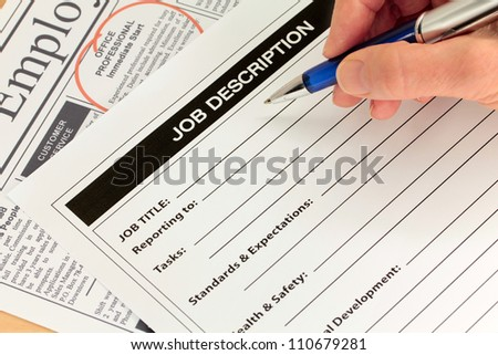 Job Description with Hand and Pen and Newspaper Ad - stock photo