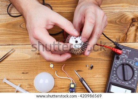 Job electrician. Male hands fixing the LEDs lamps. Workplace of electrician. Led technologies concept. Led lamp with contacts and LED board on a wooden table.  - stock photo