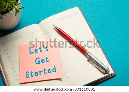 Job interview concept . Office table top view. Notepad, pen and reminder with word Let's Get Started - stock photo