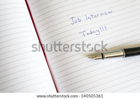 Job interview is written in the planner above the pen - stock photo