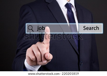 job search concept - businessman hand pressing an imaginary button over dark background - stock photo