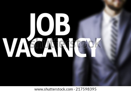 Job Vacancy written on a board with a business man on background - stock photo