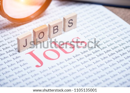 "Jobs search concept, Big red text word ""Jobs"" on white paper and Magnifying glass for jobs search"