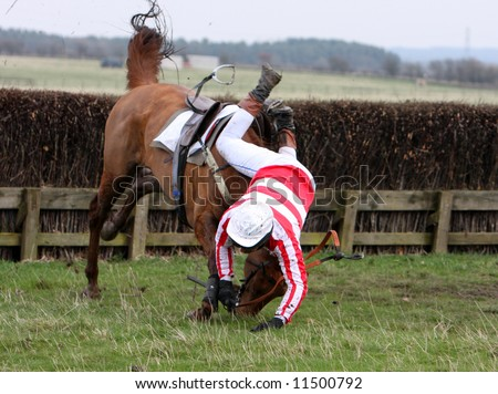 Jockey falls from his horse after jumping a jump in the race - stock photo