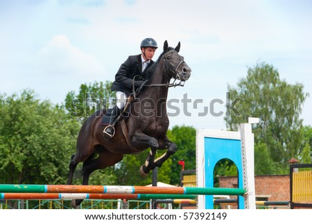 Jockey jumps over a hurdle at the competition - stock photo