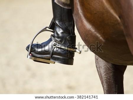 Jockey riding boot in the stirrup - stock photo