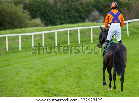 jockey standing up on race horse riding down the track - stock photo