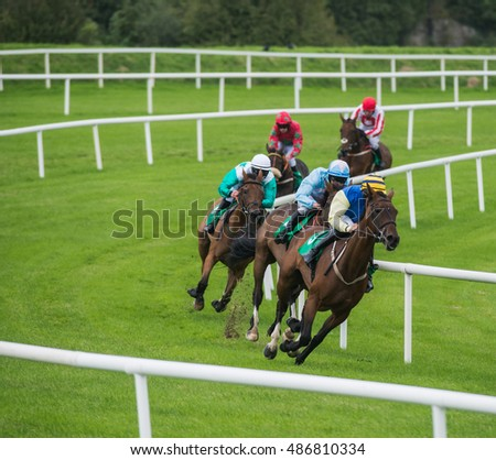 Jockeys And Race Horses Galloping Around The Bend Of Track