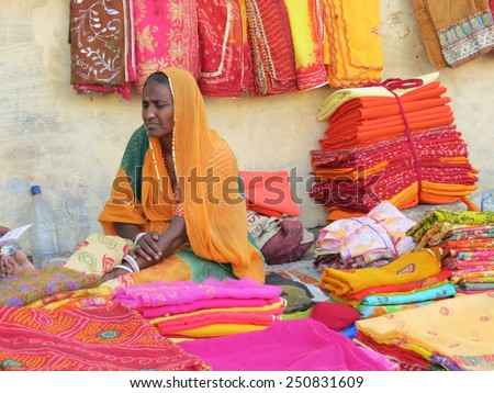 Jodhpur, India - April 1st, 2013: Indian woman selling brightly coloured saris from her pitch on the pavement. Many people sell their wares this way and the authorities seem to be okay about it. - stock photo