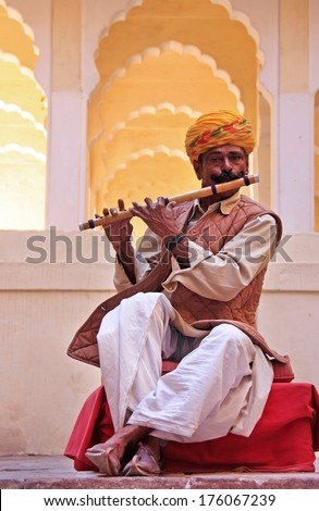 JODHPUR, INDIA - FEBRUARY 11: An unidentified man plays flute in Mehrangarh Fort on February 11, 2011 in Jodhpur, India. Mehrangarh Fort is one of the largest forts in India. - stock photo