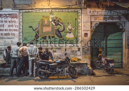 JODHPUR, INDIA - 16 FEBRUARY 2015: Elderly Indian men play cards on street while dog sleeps and motorbikes parked by. Post-processed with grain and texture. - stock photo