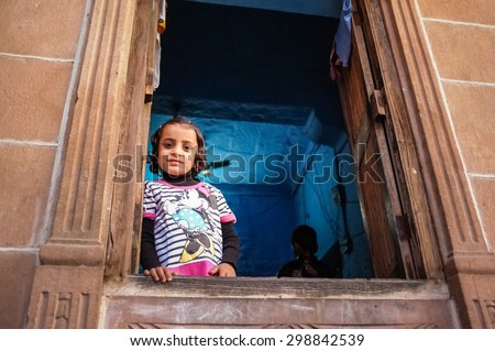 JODHPUR, INDIA - 07 FEBRUARY 2015: Little girl in Minnie Mouse shirt looking through window in blue-painted room. Common scene of blue-painted walls inside and outside of homes in old part of Jodhpur. - stock photo