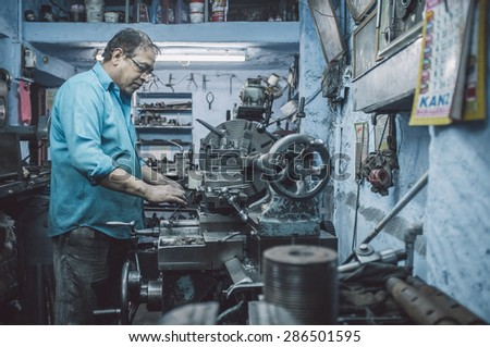 JODHPUR, INDIA - 17 FEBRUARY 2015: Mechanic working late in workshop with scattered equipment and machinery. Post-processed with grain and texture. - stock photo