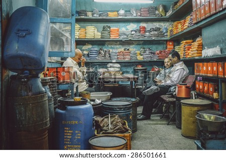 JODHPUR, INDIA - 07 FEBRUARY 2015: Owner of spice store massages forehead after long working day while customers discuss business. Post-processed with added grain and texture. - stock photo