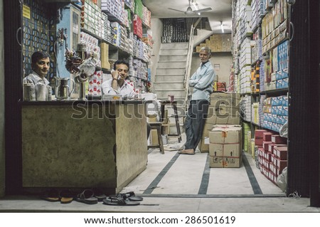 JODHPUR, INDIA - 16 FEBRUARY 2015: Three Indian men in textile store. Post-processed with grain and texture. - stock photo