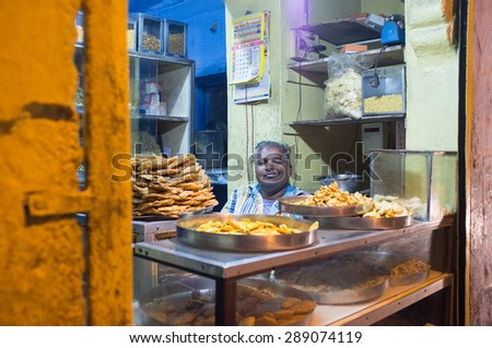 JODHPUR, INDIA - 16 FEBRUARY 2015: Vendor sits in store with food on metal plates. - stock photo