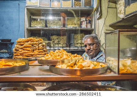 JODHPUR, INDIA - 16 FEBRUARY 2015: Vendor sits in store with various food on metal plates and noodles on shelves. Post-processed with grain and texture. - stock photo