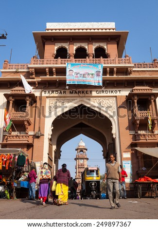 JODHPUR, INDIA - JANUARY 20, 2015 : People and rickshaws using the entrance gate to Girdikot and Sardar Markets. Jodhpur's famous clock tower can be seen through the arch in the background.