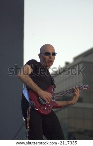 Joe Satriani and guitar - stock photo