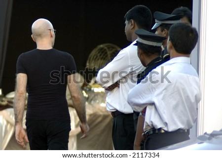 Joe Satriani walks past security guards in Bombay - stock photo