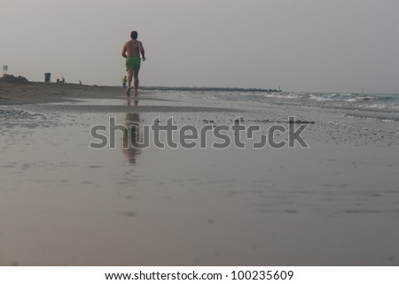 Jogger at the beach.on a very cloudy day - stock photo