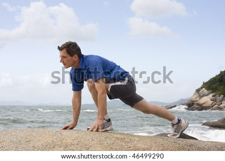 Jogger doing fitness exercises on a rock at the sea - stock photo