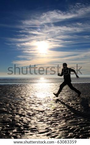 Jogger on the beach - stock photo
