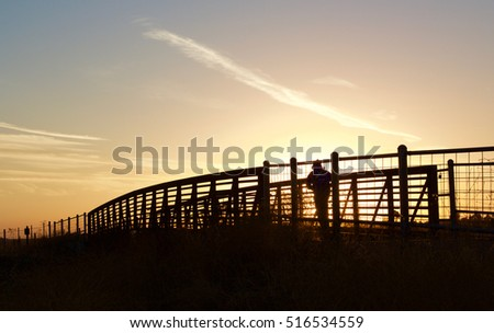 Jogger on Walkway-a silhouette of a lone jogger crosses a wooden footbridge during the setting sun