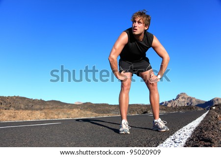 Jogger resting after running. Man runner taking a break during training outdoors in amazing landscape. Young Caucasian male fitness model after work out. - stock photo