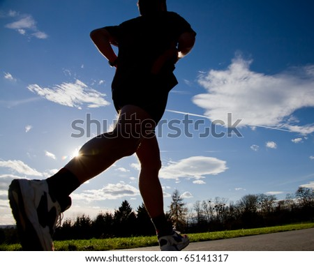 jogger running in back light - stock photo