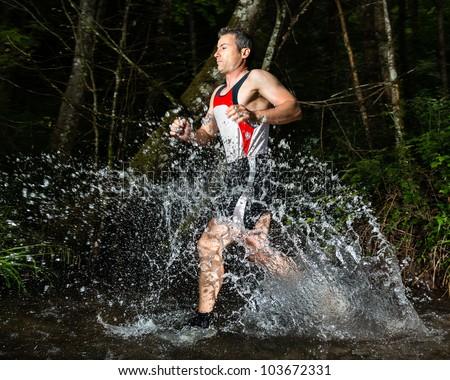 jogger running through a streambed - stock photo