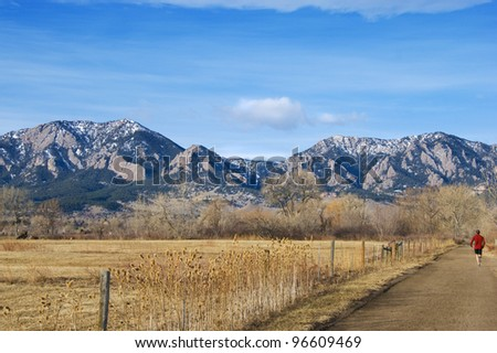 Jogger runs along the side of a golden field on the Colorado prairie near Boulder, with tall mountains in the distance. - stock photo
