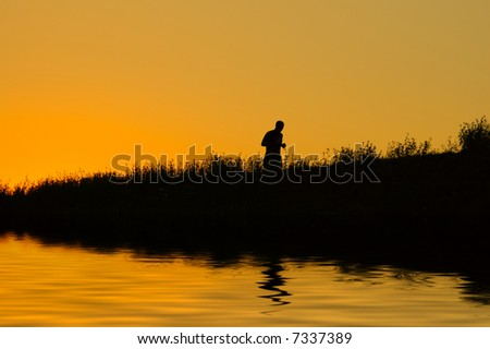 Joggers silhouette at sunset - stock photo